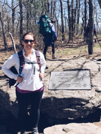 Hiker at Appalachian Trail plaque at Springer Mountain